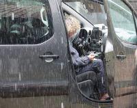 0005_Mieke_Bouman_noteert_de_gegevens_in_de_stromende_regen_vanuit_de_auto